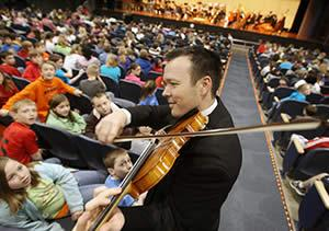 Violinist Nathan Seaman demonstrates his instrument as students prepare for the performance